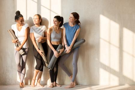En una mañana soleada, hermosas chicas diversas se reunieron en el gimnasio para hacer ejercicio. Cuatro mujeres delgadas en ropa deportiva de pie descalzas cerca de la pared sosteniendo esteras de yoga hablando se sienten felices. Concepto de bienestar de entrenamiento grupal