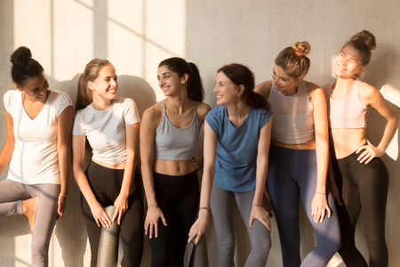 Six attractive different slim girls standing together in a row talking enjoy pleasant conversation. Multiracial women in activewear with yoga mats waiting workout at sports studio in the sunny morning 版權商用圖片