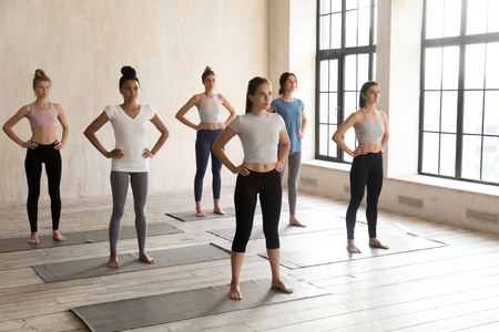 Five diverse attractive positive slim women wearing sports top and leggings standing in rows barefoot on rubber carpets ready starting exercises at fitness club. Active and healthy lifestyle concept Stock Photo