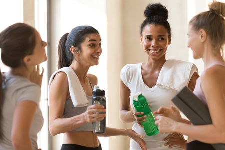 Beautiful young sporty girls talking standing in yoga class, focus on mixed race and indian females. Women resting enjoying conversation finished workout. Healthy lifestyle and group training concept