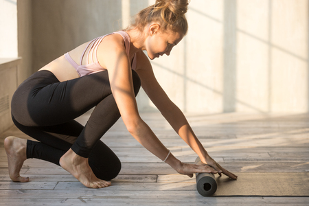 Attractive yoga instructor is preparing for session unrolling rubber carpet in light cozy room. Sportive woman wearing sport bra and pants finished workout folding mat after training at fitness club Stock Photo - 114277762