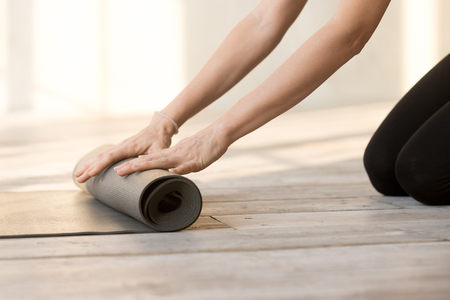 Close up woman hands unrolling mat is preparing for fitness workout at studio. Female folding rubber carpet after yoga session finished sport training. Wellness and active healthy lifestyle concept