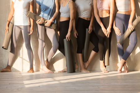 Six slim females wearing sportswear sports tops and leggings standing barefoot near wall in row holding yoga mats, women body without faces, sunlight through window in the morning. Wellness concept Banco de Imagens - 114277770