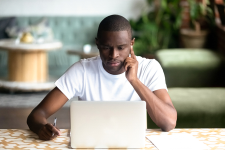 Focused African American man using laptop in cafe, serious black student looking at computer screen, thinking about online project, task, reading e-book, news, journalist writing, think about article
