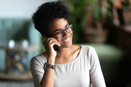 Happy African American woman talking on phone, having pleasant conversation with friend, holding cellphone, speaking, chatting by smartphone in cafe, smiling female receive good news, making call Stock fotó - 114277642