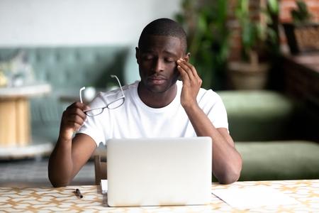 Homme afro-américain fatigué enlevant des lunettes, ressentant une fatigue oculaire après un long travail avec un ordinateur portable, un ordinateur, un étudiant épuisé surmené dans un café, assis les yeux fermés ayant un problème de mauvaise vision Banque d'images