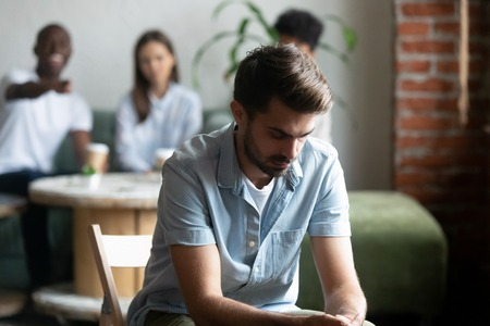 Upset frustrated young man suffering from gossiping, bullying, discrimination, avoiding, ignoring, having problem with bad friends, feeling offended and hurt, sitting alone in cafe