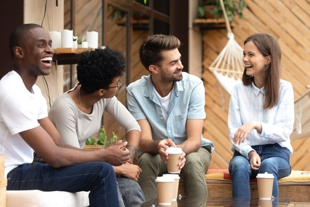 Diverse multiethnic friends laughing at young woman joke, sitting at cafe table, colleagues or students drinking coffee, having fun, spending time together, talking, discussing funny news