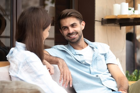 Happy smiling handsome man having good conversation with young woman, boyfriend looking at girlfriend, having fun together, first date concept, friends share thoughts, pleasant news in cafe Stock Photo