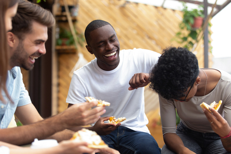 Happy multiethnic friends eating pizza, Italian junk food together in cafe, laughing at joke, funny news, having fun together at meeting, excited colleagues sharing meal at lunch, hanging out together