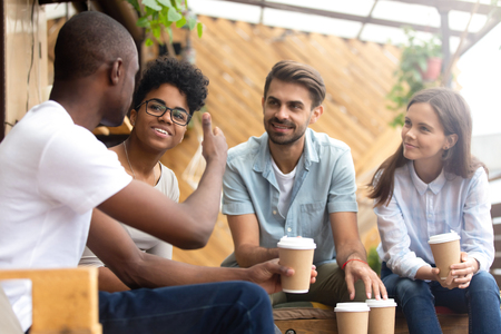 African American man showing thumb up, telling story to interested attentive friends, sitting, drinking coffee in cafe together, smiling multiethnic friends discussing, talking, chatting Фото со стока