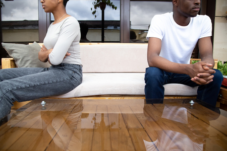African American couple sitting on couch separately after quarrel in cafe close up, upset woman with arms crossed ignoring serious man looking in distance, no desire to talk, break up concept