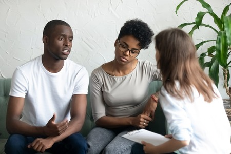 Unhappy young African American couple visiting psychologist, upset man talking about relationships problem with tired frustrated woman, family therapy session, husband and wife sit on couch together