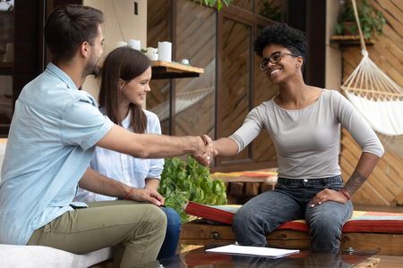 Young happy couple signing contract with realtor or wedding planner in cafe, excited man shaking hand of African American female financial advisor, mortgage agreement, good deal, happy clients Archivio Fotografico