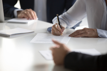 Businesspeople gathered together at business meeting after successful negotiations ready to sign agreement official paper close up focus on businesswoman hands holds pen affirm contract with signature.