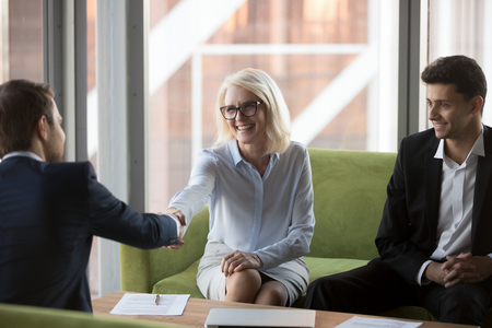 Attractive smiling old business woman executive manager shaking hands with company partner greeting each other and expressing regard. Diverse businesspeople gathered together ready to signing contract
