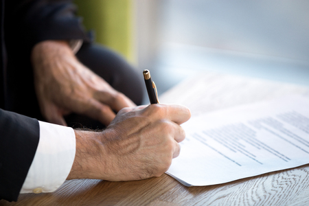Confident businessman sitting in office desk holding pen puts his signature on official document, close up of male hands and table. Beneficial cooperation, important decision, financial deal concept Stock Photo
