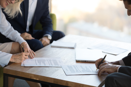 Mature businesswoman and middle eastern ethnicity businessman sign contract after negotiating close up focus on contract agreement lawful paper on a table. Collaboration between businesspeople concept Stock Photo