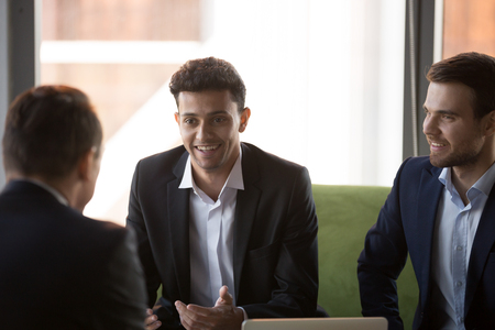 Positive middle eastern ethnicity businessman take break talking with colleagues during workday. Diverse well-dressed business partners wearing suits discussing share ideas at meeting in modern office