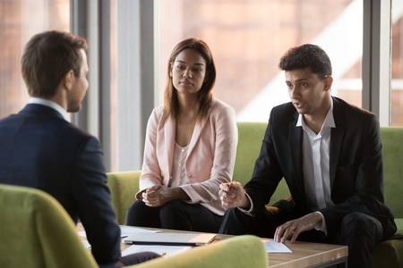 Serious biracial businesswoman and middle eastern ethnicity business partners listening caucasian businessman sitting in comfortable couches negotiating discussing startup new project in modern office Stock Photo