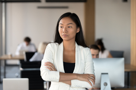 Head shot of serious asian woman stands in coworking office with hands crossed feels dissatisfaction. Pensive businesswoman company employee having difficulties at work thinking about problem solving