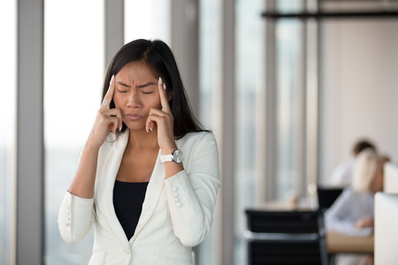 Asian young woman with closing eyes touch massage temples feels herself unhealthy suffers from headache migraine in office. Millennial stressful unhappy employee having difficulties problems at work