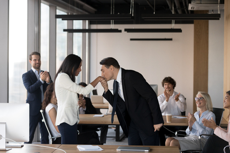 Aged company owner kissing the hand of asian young surprised female, expressing showing regard and gratitude congratulate worker with successful work, diverse coworker looking at them and applauding Stock Photo