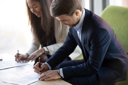 Positive asian businesswoman sitting on couch with business partner, focus on caucasian businessman, people signing contract agreement document. Successful negotiations, trust and partnership concept