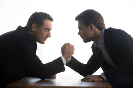 Side view of senior aged and millennial young businessmen in formal suits holds elbows on table arm wrestling at office workplace looking eyes to eyes face to face struggling for leadership at work. Banque d'images - 114277277