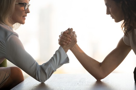Side view close up young brunette and aged blond businesswomen arm wrestling holds elbows on table, exerting pressure on each other, looking eyes to eyes face to face struggling for leadership at work Stok Fotoğraf