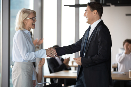 Middle aged excited employee getting reward shake hands with company boss. Executive manager congratulates best worker of the month handshaking with happy experienced colleague standing in coworking Banco de Imagens