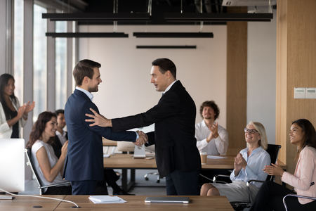 Mature director company owner congratulating young specialist handshaking standing at coworking area, diverse multiracial coworkers different colleagues applauding rejoicing for success of colleague