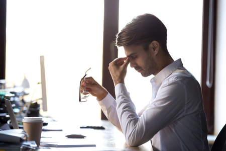 Fatigued exhausted businessman taking off glasses feeling headache, tired eyes concept, overworked man massaging nose bridge to relieve dry irritated eyes suffering from eye strain problem at work
