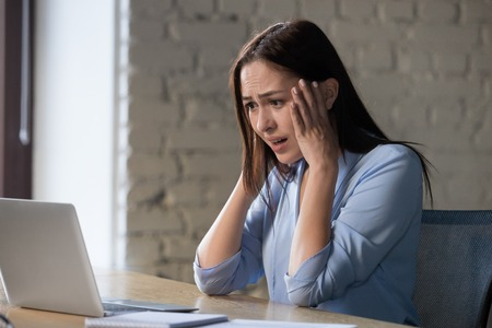 Shocked woman feels desperate reading bad internet or email business news, scared stressed lady terrified with online cyber bullying afraid of stuck computer error problem looking at laptop screen Imagens