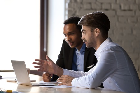 Financial advisor insurer speaking consulting african client looking at laptop making presentation, caucasian mentor teaching black intern, employees colleagues help discuss online computer project