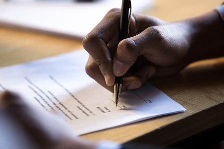 Male african hand signing financial contract concept, black businessman put write signature on legal corporate paper fill document form buy insurance loan, making business agreement, close up view 免版税图像