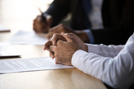 Lawyer solicitor with clasped hands consulting client about document making financial legal deal sell law services, close up view of business counselor or agreement party at contract signing concept