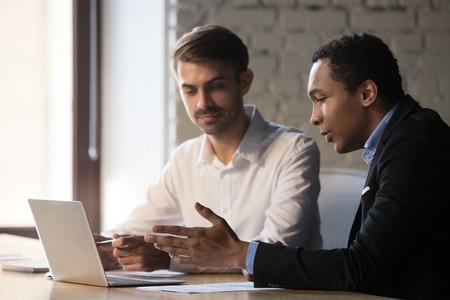 Asesor de mentor de gerente africano que enseña a un pasante de cliente caucásico que muestra un nuevo proyecto en línea dar una presentación en una computadora portátil, un asesor negro que habla ayudando al cliente a explicar el trato apuntando a la computadora Foto de archivo