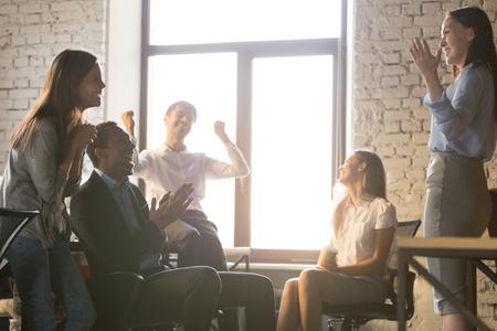 Aufgeregte, vielfältige Teamleute, die den Erfolg feiern und den Führer unterstützen, großartige Neuigkeiten zu erzählen, die Verkaufsgruppe der glücklichen multiethnischen Mitarbeiter, die dem Kollegen mit Geschäftserfolg oder Belohnung gratuliert Standard-Bild