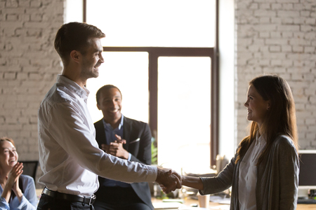 Male team leader handshaking female excited employee congratulating hiring intern with promotion business achievement, thanking for good work result expressing respect support, recognition rewarding