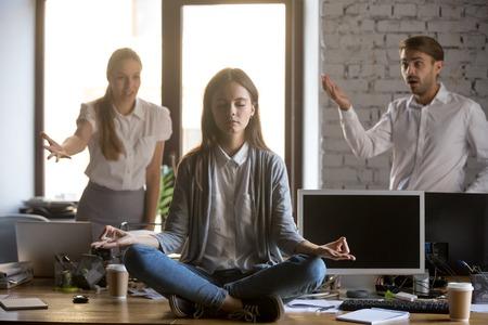 Impiegato calmo e sereno che medita in ufficio ignorando il non ascolto di colleghi fastidiosi, giovane lavoratrice divertente che fa yoga evitando lo stress sul lavoro per il concetto di controllo emotivo dell'equilibrio mentale