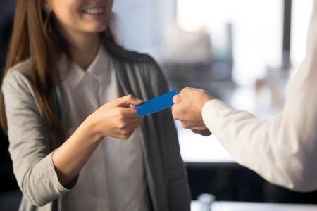 Homme d'affaires remettant une carte de visite de visite pour une femme d'affaires client partageant des informations personnelles, une introduction, un échange de contacts et un concept de mise en réseau, vue rapprochée