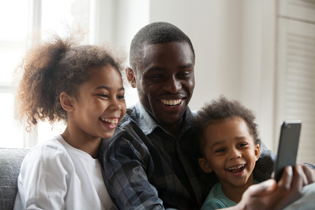 Happy african american dad laughing using smartphone with little son daughter at home, black daddy and children make call selfie watching funny video on phone, family father and cute kids having fun