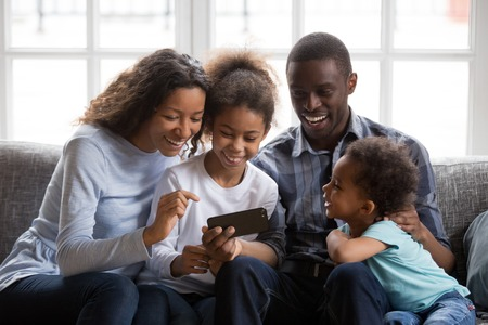 Black african family of mom dad parents and happy 2 mixed race little kids sit together on sofa laughing looking at smartphone taking selfie, making video call, watching funny video on phone at home Stok Fotoğraf