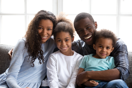 Happy black family of four dad mom and little son daughter, loving african mother father embrace 2 mixed race children sitting on sofa with parents looking at camera, kids mum daddy at home portrait Фото со стока