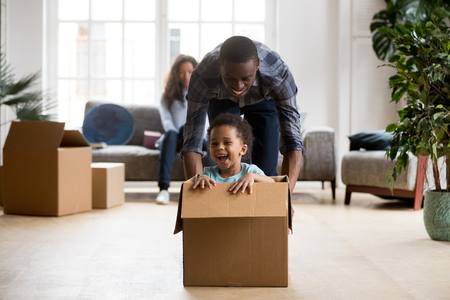 Cute little mixed race son laughing excited by riding in box with african dad on moving day, happy father plays with kid boy after relocation, black family and child have fun in new home living room 版權商用圖片