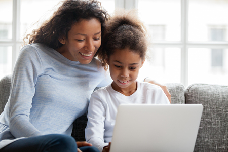 Smiling african american mother and kid daughter have fun shopping online at home, happy black mom teaching little mixed race child girl learn use laptop, watch cartoon, make video call on computer Stock Photo