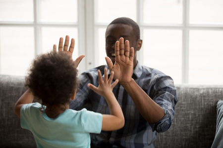 Happy black dad playing patty cake with little son at home, excited african single father and toddler cute kid boy laughing giving high five, daddy child enjoying clapping hands having fun together Banco de Imagens