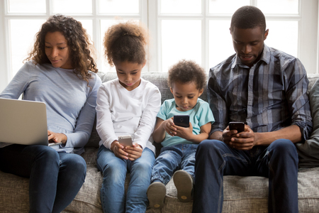 African american family with kids using laptop and mobile phones at home, black parents and little children addicted to devices, gadgets dependence overuse, internet social media addiction concept