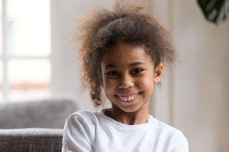 Cute funny little african american girl looking at camera, smiling mixed race child posing for portrait at home, preschool positive black kid with happy face headshot, orthodontic malocclusion Stock Photo